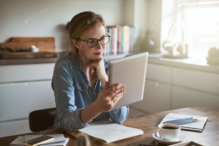 Focused young entrepreneur working online in her kitchen