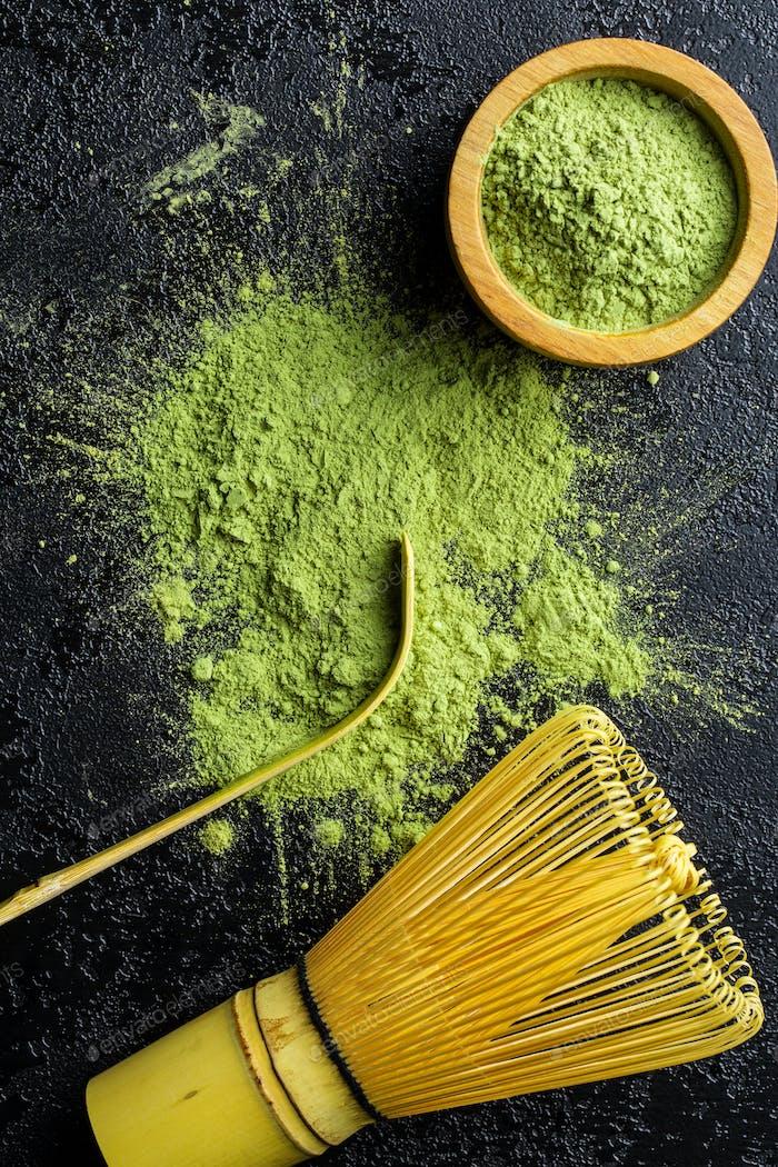 Grünes Matcha-Teepulver mit Bambusbesen, Löffel und Schüssel.
