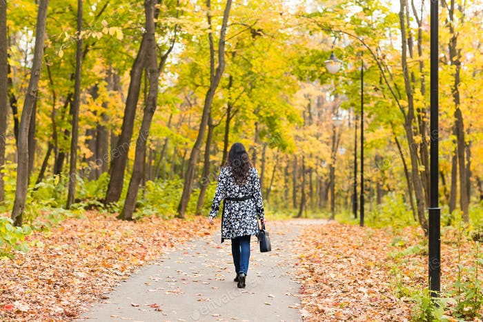 Pretty young student girl in autumn outdoor.