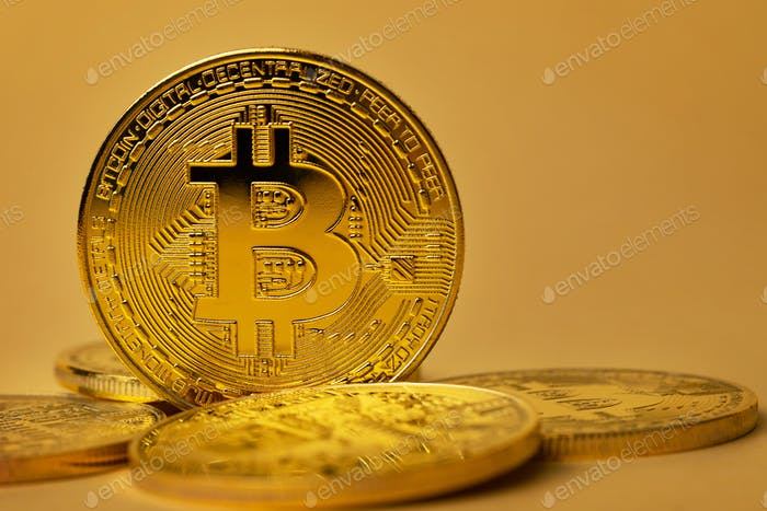 Closeup of shiny gold bitcoin on yellow backgound
