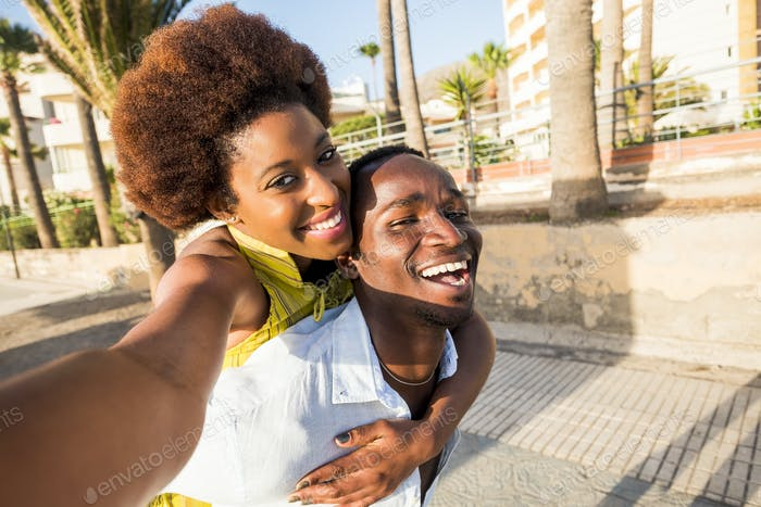 black race african american couple having fun and joking playing together on the walk