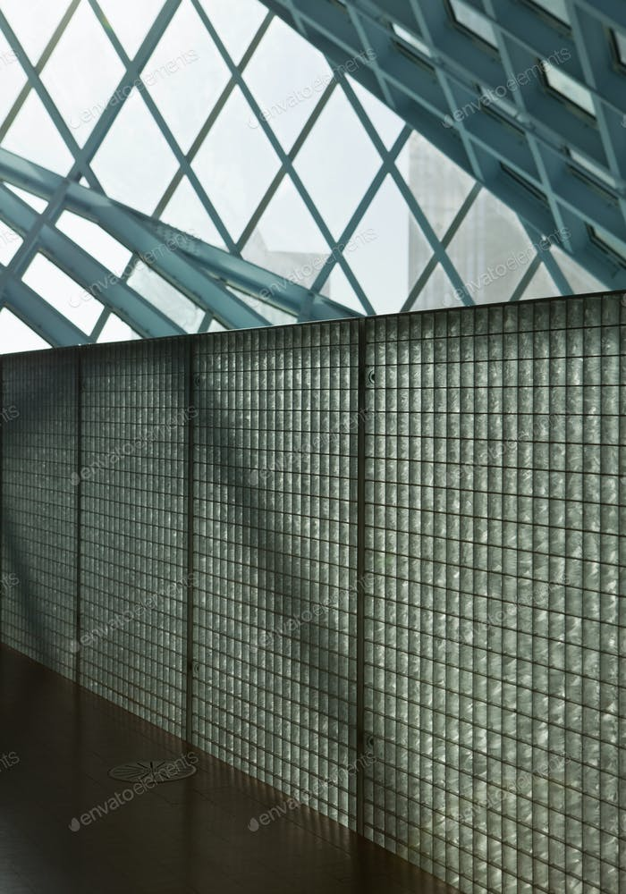 Building interior, sloping glass roof panels, barrier, fence with square metal barrier.