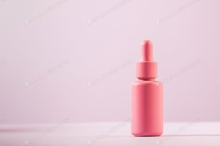 A mockup of a pink dropper with a facial serum on a pink background. Trends in facial skin care.