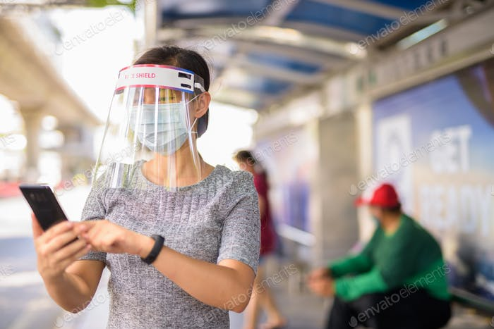 Young Asian woman with mask and face shield using phone at the bus stop
