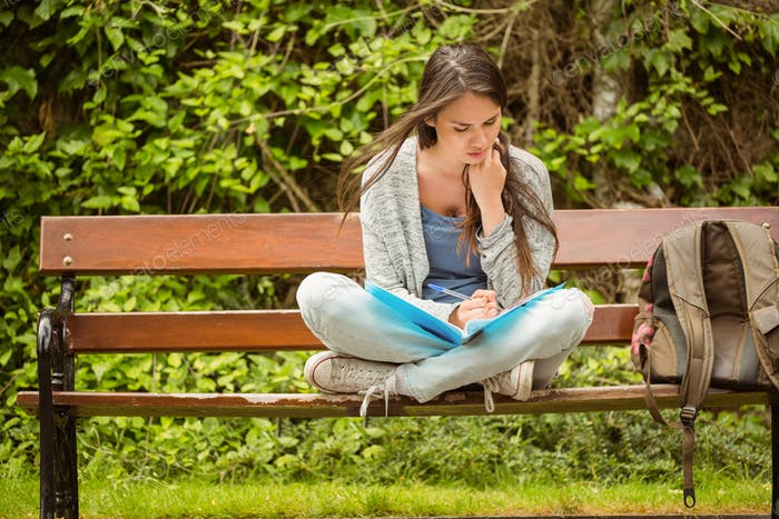 Smiling student sitting on bench reading book in park at school
