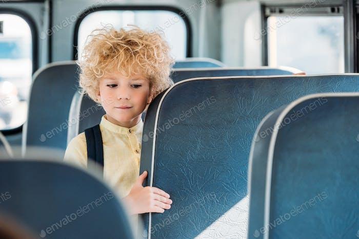 adorable curly schoolboy standing alone in school bus