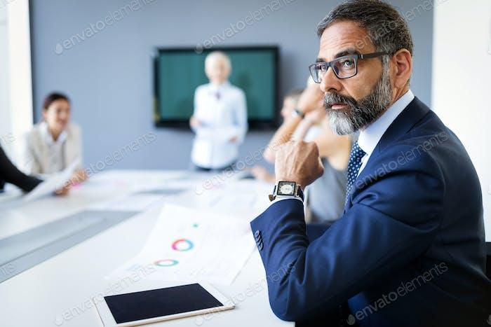 Portrait of handsome senior businessman with digital tablet in the modren office