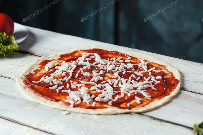 Closeup of a home made raw pizza with cheese and tomato sauce on a wooden background