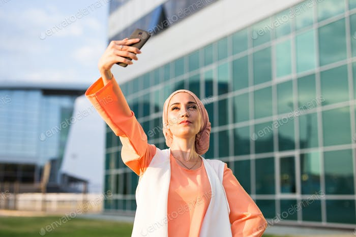 Arabian muslim islamic woman taking selfie on smartphone outdoors