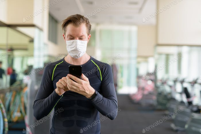 Young man using phone with mask for protection from corona virus outbreak at gym during corona virus