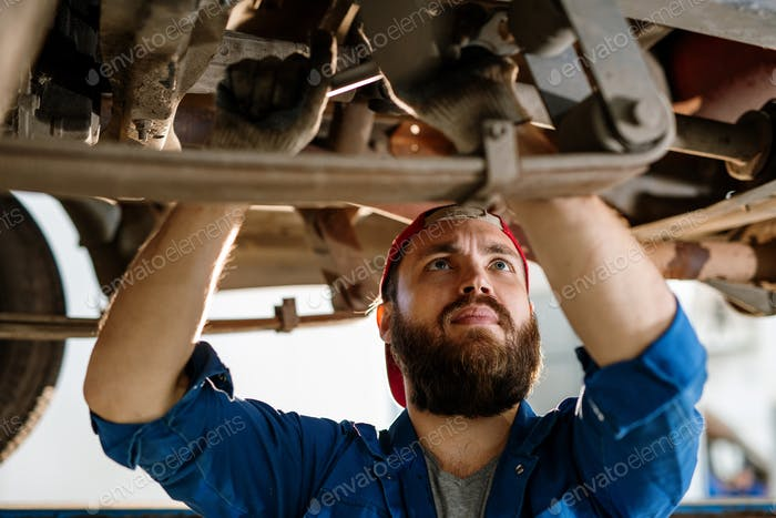 Bearded worker of technical service concentrating on examination of car engine