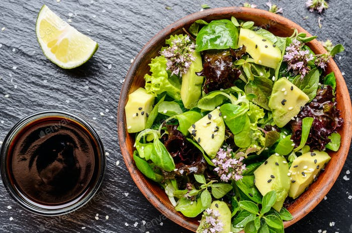 Draufsicht auf Tongericht mit Salat aus Avocado, grün und violett