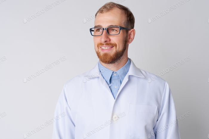 Portrait of happy young bearded man doctor with eyeglasses thinking