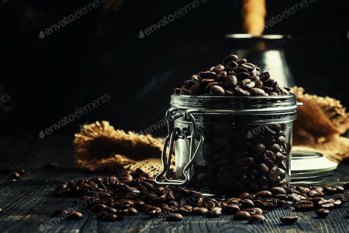 Grains of roasted arabica coffee in a jar