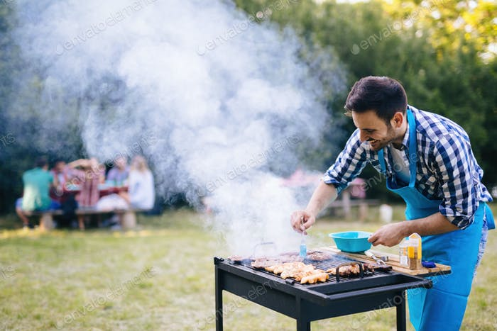 Handsome man preparing barbecue
