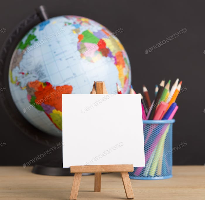 Close up of white blank easel for writing text, world globe