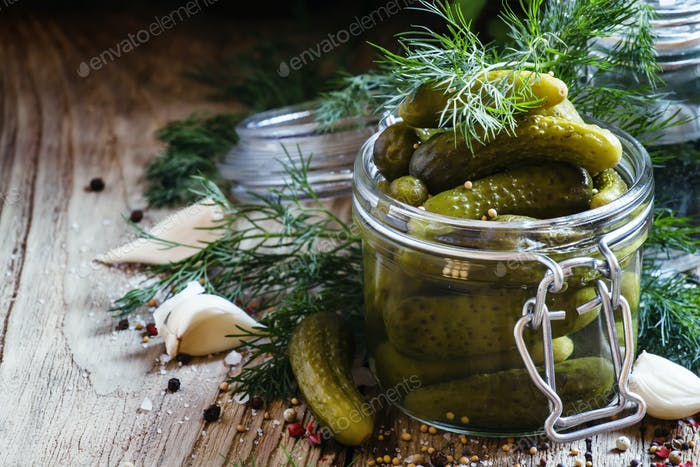 Pickled small cucumbers gherkins in a glass jar with dill, herbs and spices