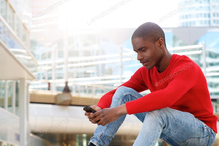 african american man sitting outside using mobile phone