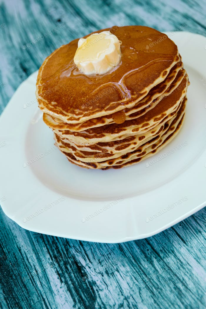 Top view of pancakes with butter and honey or maple syrup on white plate on blue wooden background.