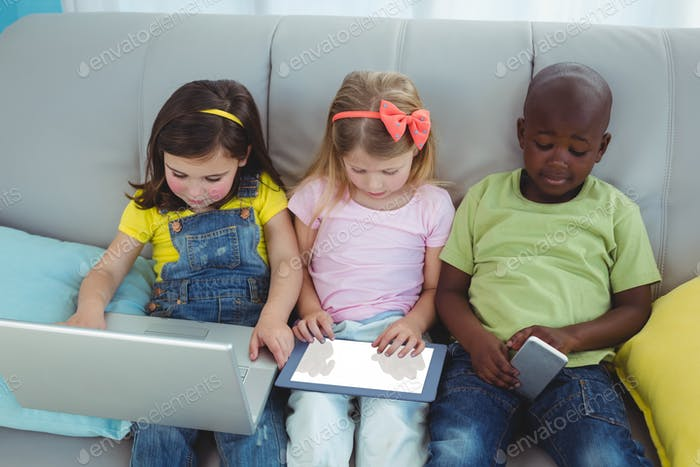Happy kids sitting together with a tablet on the couch