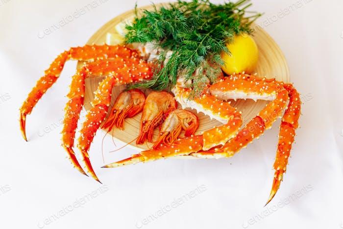 Garnelen, Krabben, Zitrone und Grüns auf einem Teller auf weißem Hintergrund.