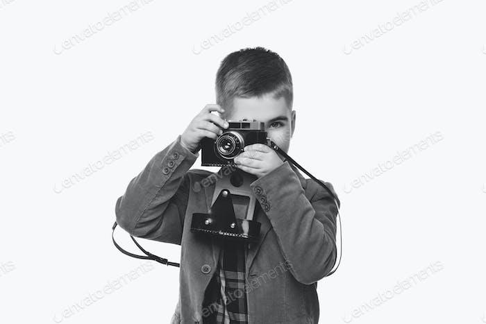 Schöner junger Junge mit Retro-Kamera