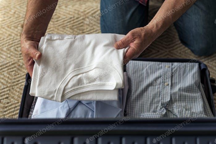 Draufsicht auf Mann packenKleidung im Koffer immer bereit für den Urlaub.