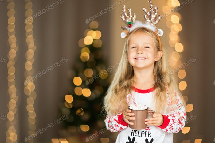 Happy Caucasian Girl With Blonde Hair in Christmas Pajamas Holding Cup of Cocoa at Home