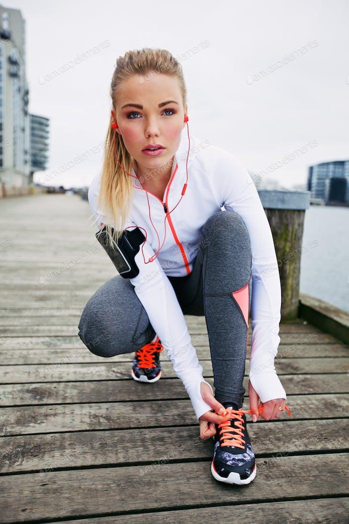 weiblich Athlet binden Ihr Schnürsenkel vor ein run