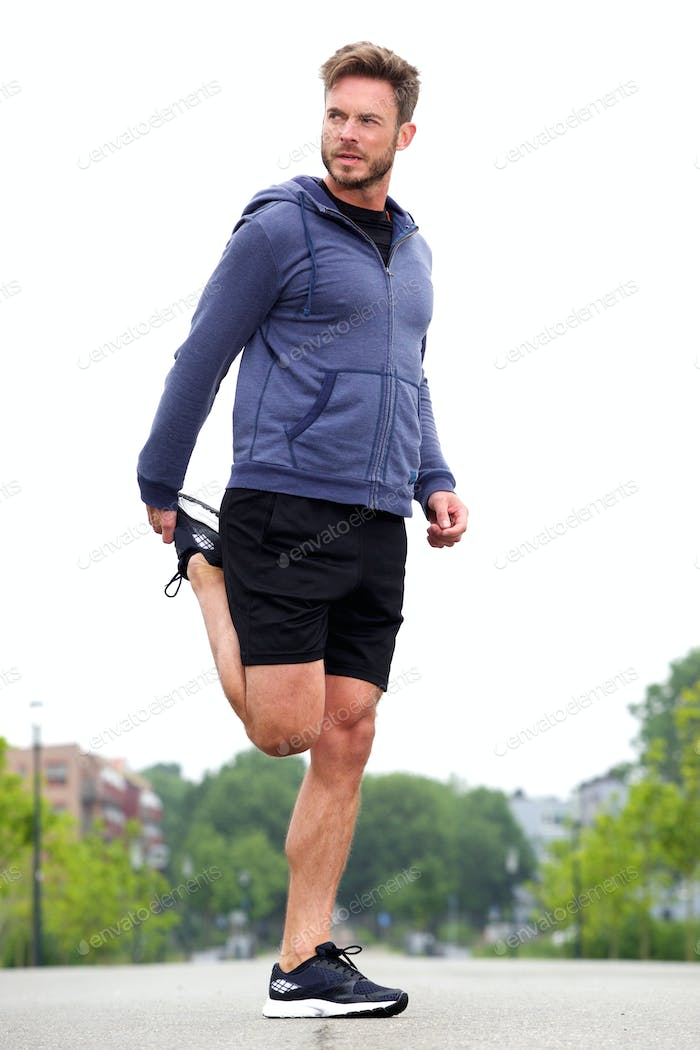 Attractive man doing stretch in street before run