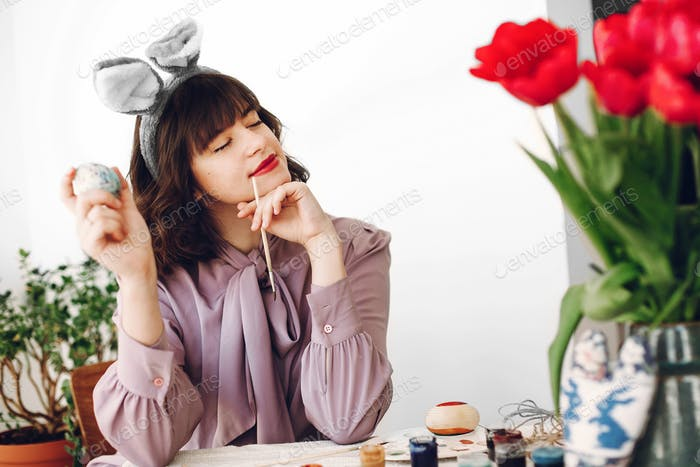 Beautiful stylish girl in bunny ears smiling and painting easter eggs