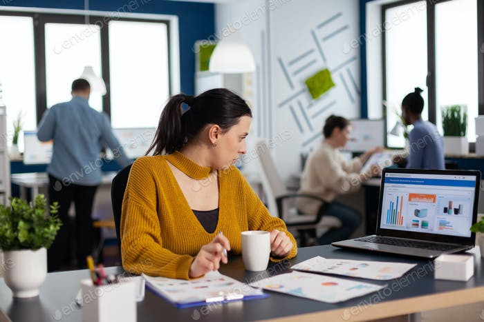 Businesswoman sitting at desk in office analyzing charts