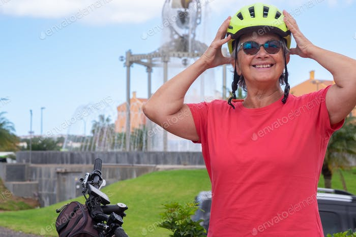 Youthful senior woman in activity with bicycle in urban park wearing a yellow protective helmet