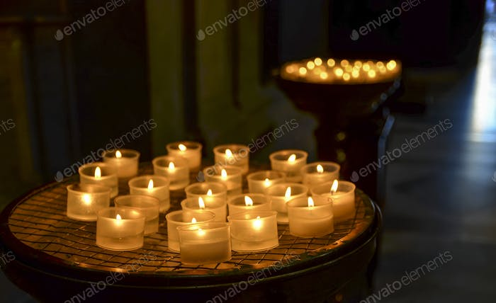 Close up of lit candles in a church in Rome, Italy.