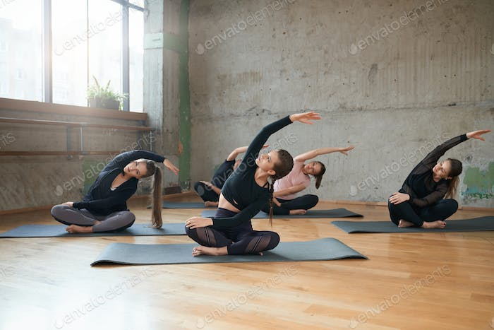 Gruppe von Frauen Stretching in Lotus-Pose in der Halle