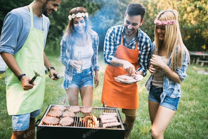 Friends spending time in nature and having barbecue