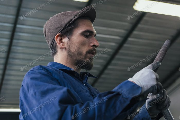 Ernsthafte Handwerker hält Eisen Details
