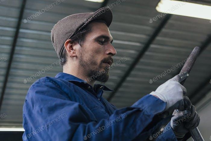 Serious craftsman holding iron details