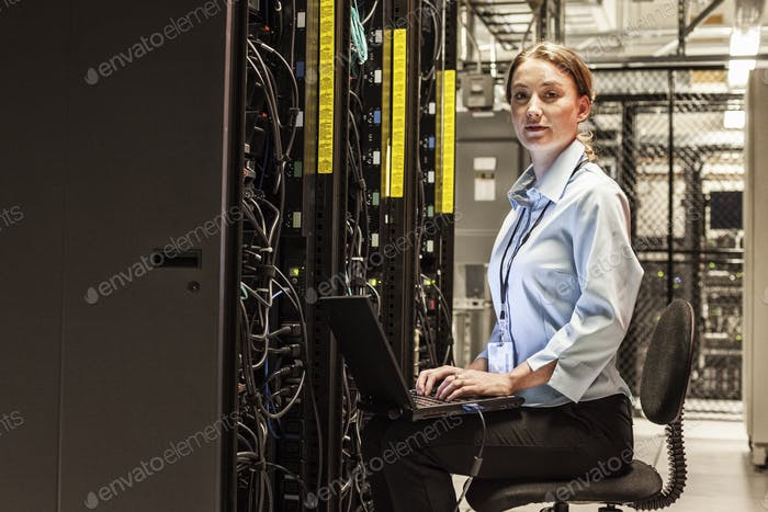 Caucasian woman technician working on computer servers in a server farm.
