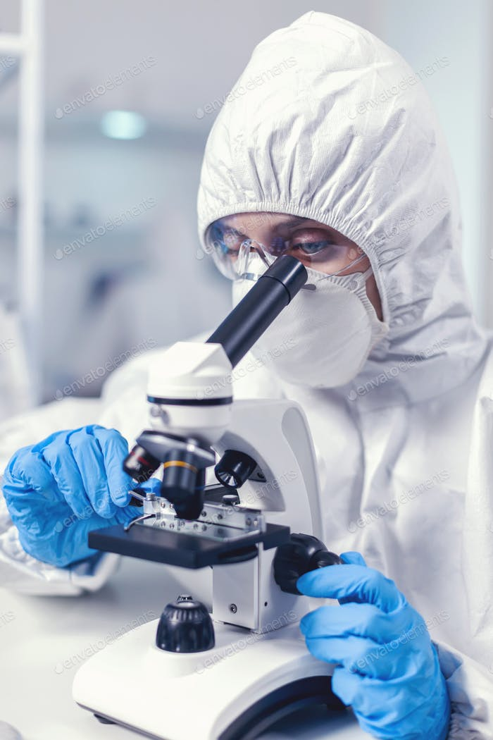 Woman scientis in coverall doing coronavirus investigation
