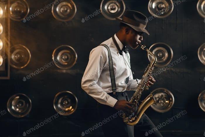 Black jazzman in hat plays the saxophone on stage