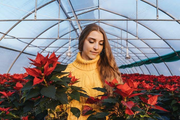 Woman in greenhouse in yellow sweater