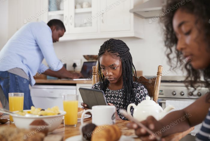 Family Sitting Around Breakfast Table Using Digital Devices