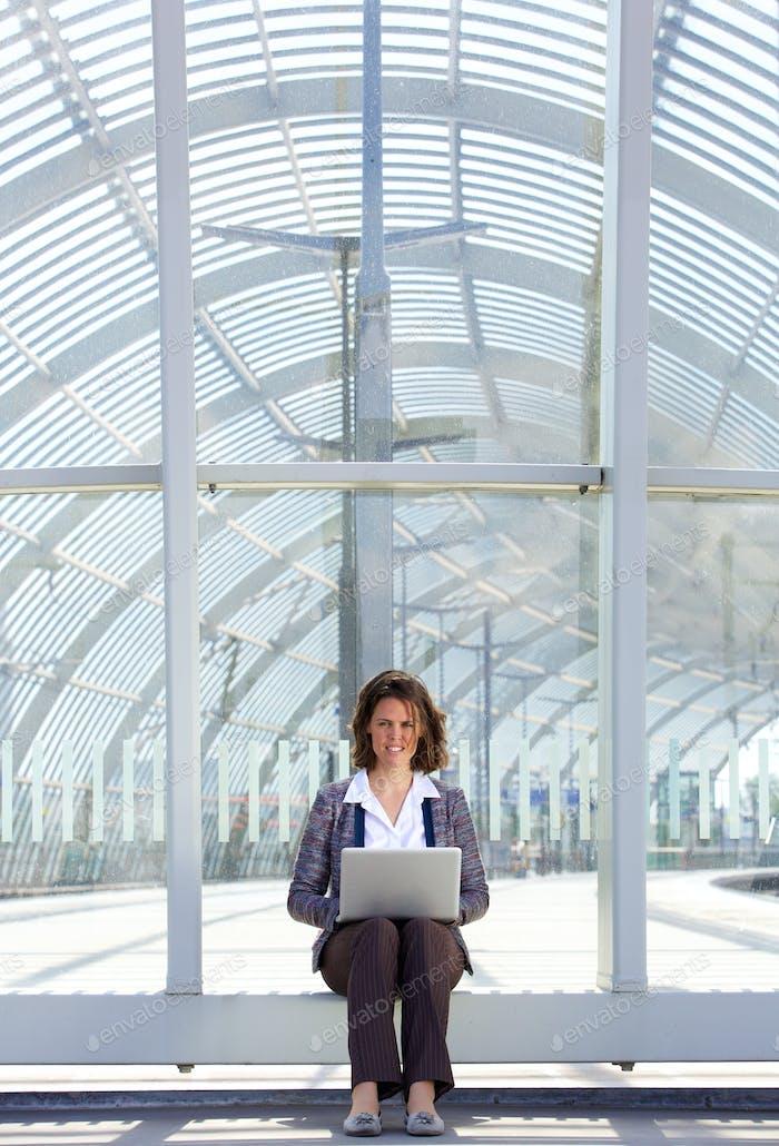 Lächelnde Geschäftsfrau sitzen draußen mit Laptop
