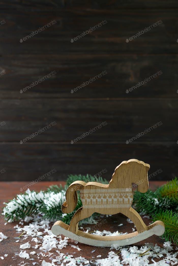 Spielzeug Holz Schaukelpferd ab Neujahrsschmuck mit Schnee und Fer Baum auf einem hölzernen Hintergrund