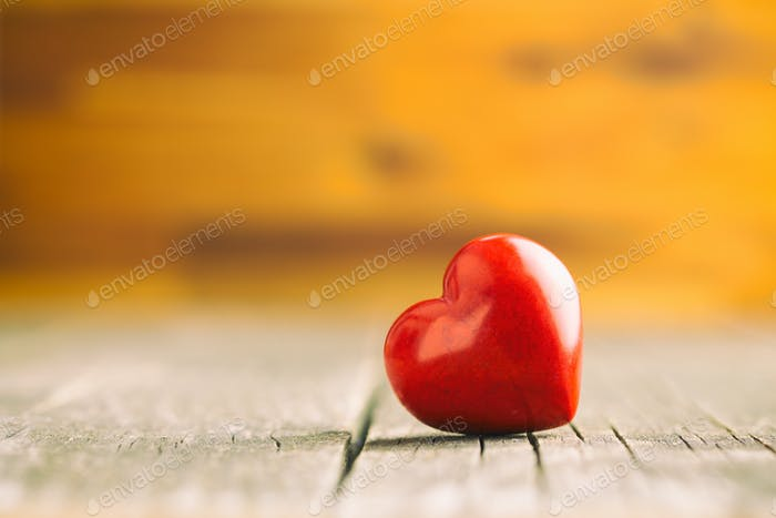 Red heart on wooden table.