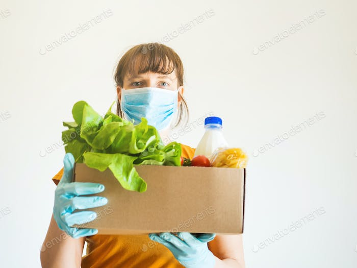 Woman in face mask with food delivery box