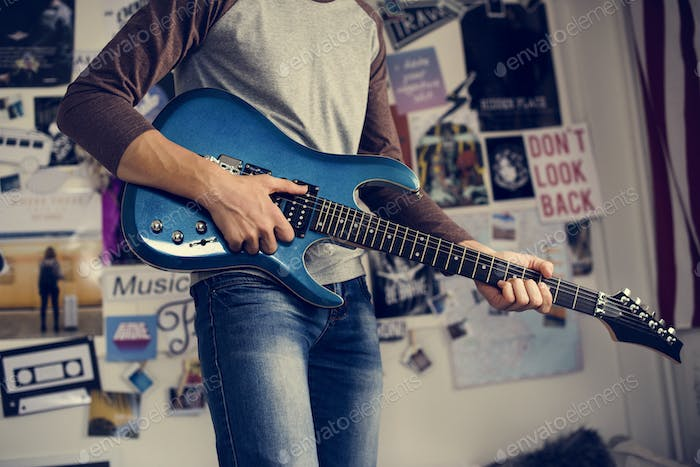 Teenage boy playing an electric guitar in a bedroom hobby and mu