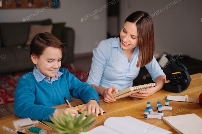 Обучение на дому, обучение женщины и мальчика за столом
