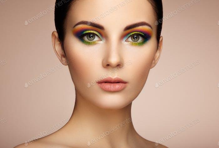 Porträt einer schönen jungen Frau mit Regenbogen-Make-up